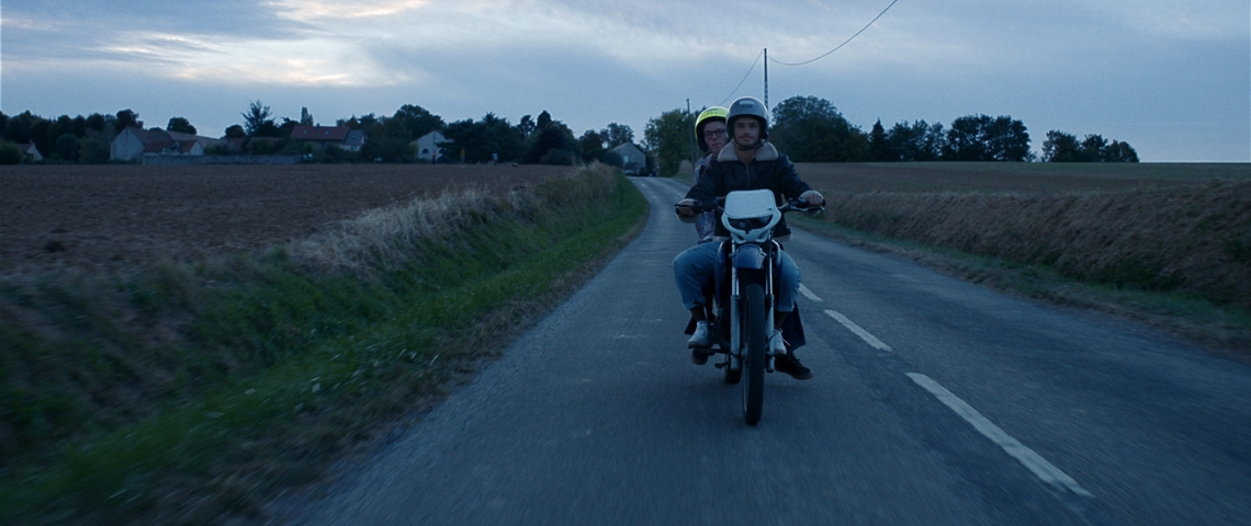 Deux hommes sur un scooter sur une route de campagne
