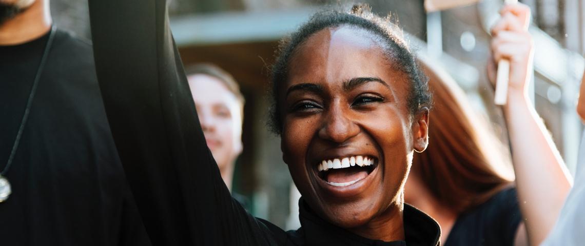 Une femme noire manifeste aux côtés de ses camarades manifestants