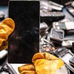 deux mains gantés démontent un smartphone