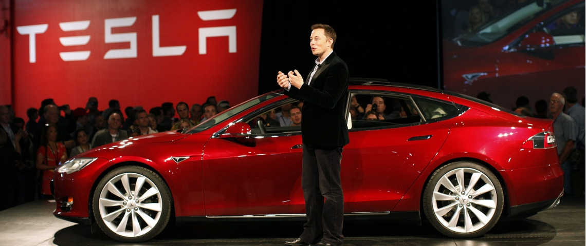 Elon musk devant une Tesla rouge