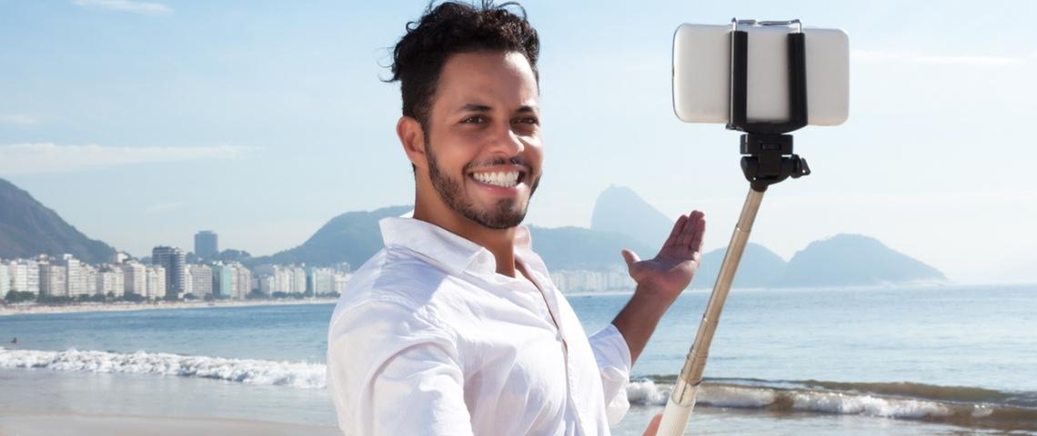 Jeune homme à la plage, se prenant en photo avec une perche à Selfie