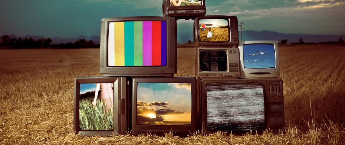 Des télévisions allumées au milieu d'un champ rasé
