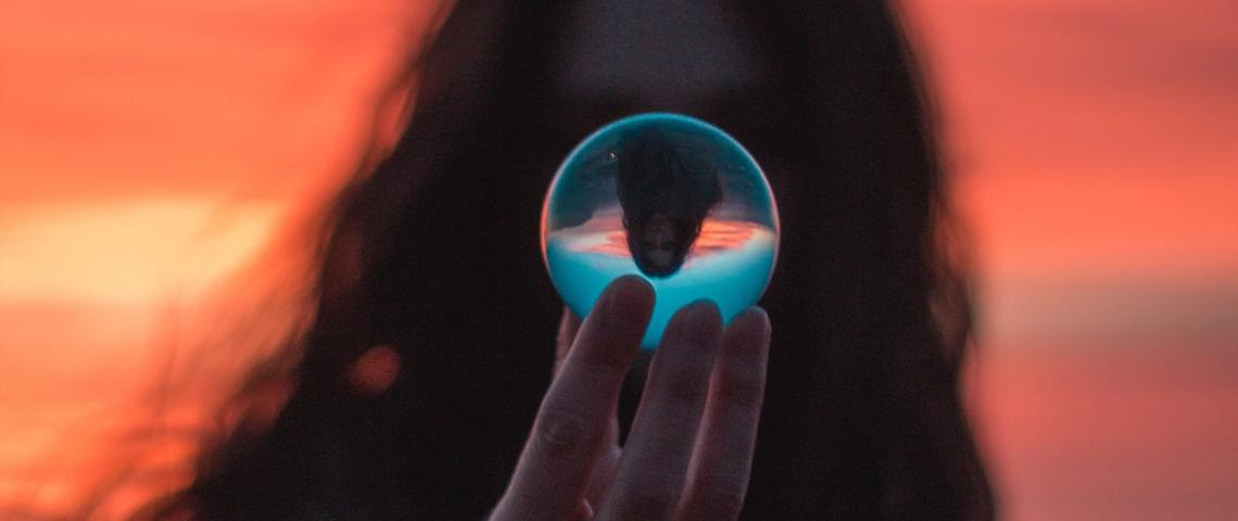 une femme tient une boule de cristal devant son visage