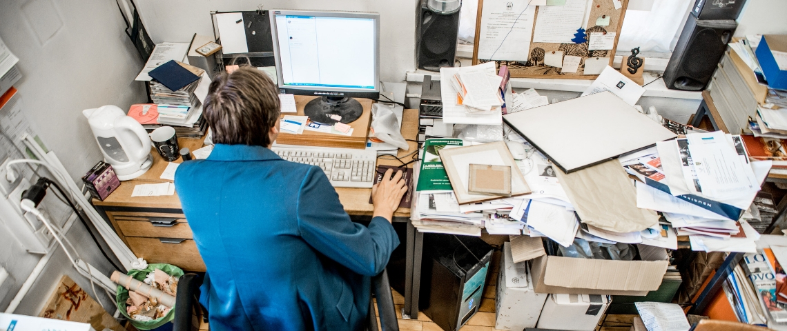 Un homme de dos, assis à son bureau mal rangé