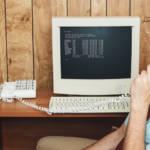 Un homme interloqué au téléphone, derrière un ordinateur rétro