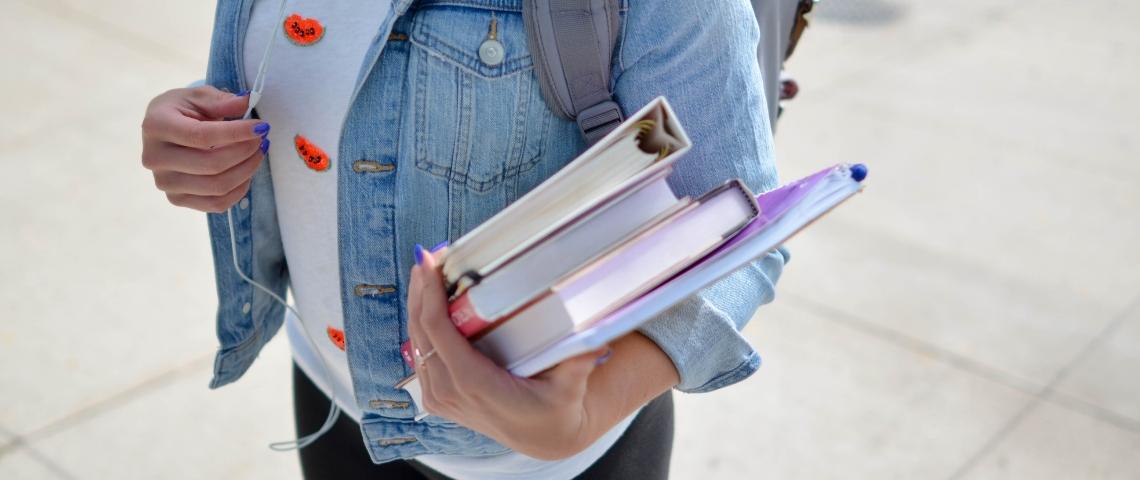Une étudiante qui porte ses livres de classe