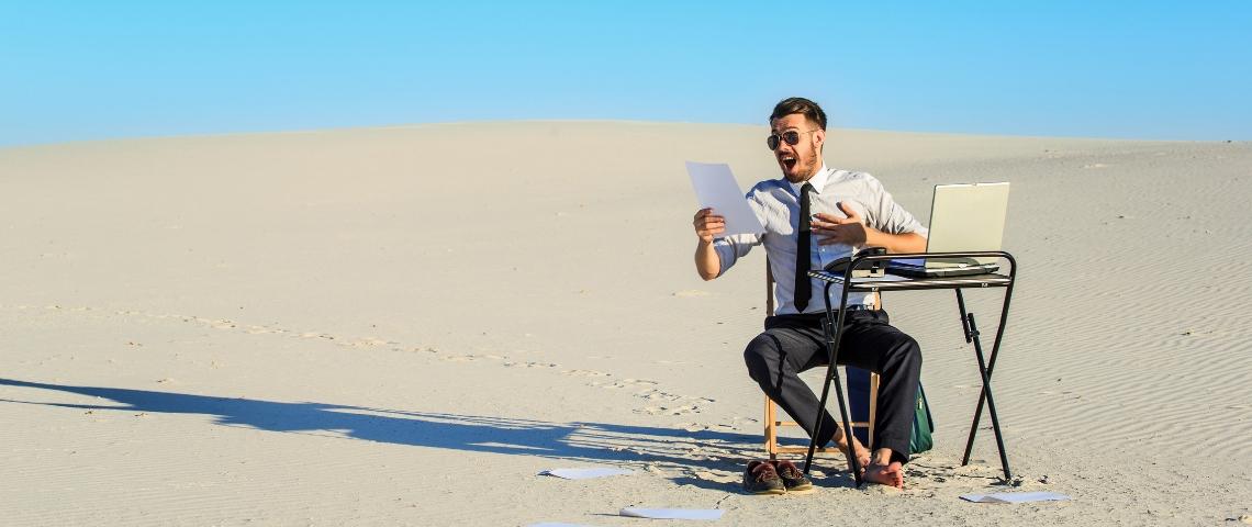 Un homme, seul, assis à un bureau dans le désert