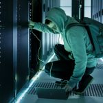 Une personne en capuche s'occupe d'un data center