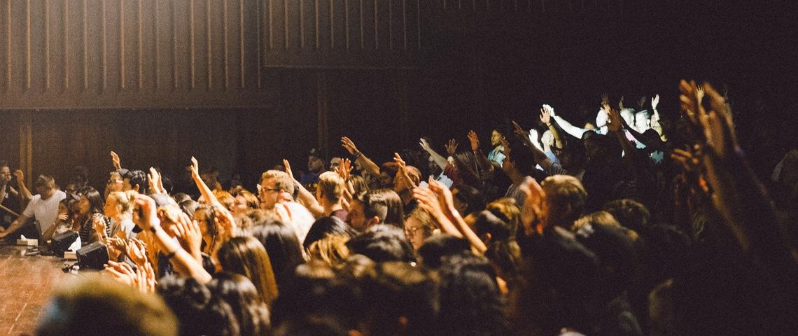 assemblée de personnes levant la main