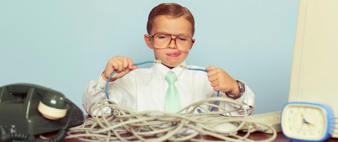 Un enfant habillé en tenue de travail dans un bureau en train d'essayer de brancher deux câbles