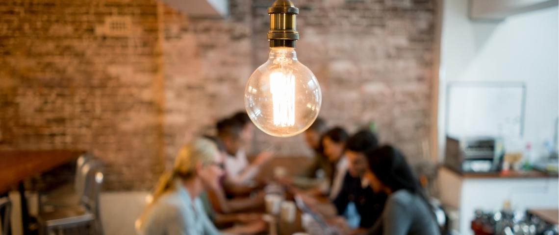Une ampoule sur fond flouté de personnes qui travaillent sur un bureau