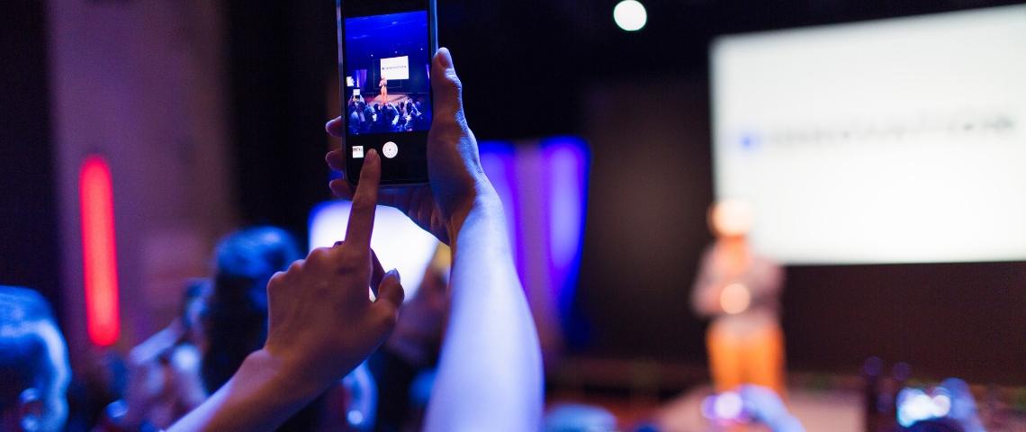 Une personne en train de photographier une prise de parole scénique avec son téléphone portable