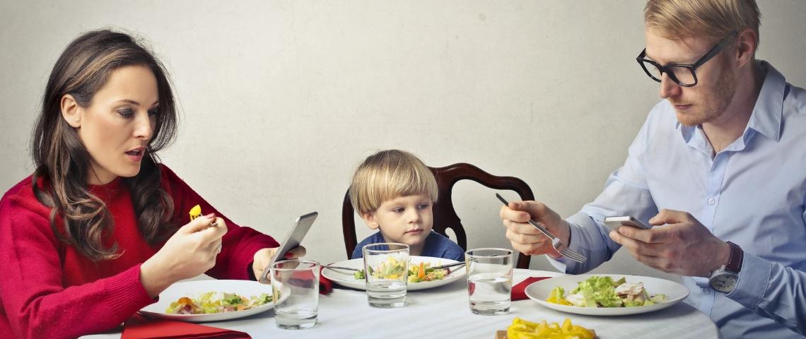 Un homme et une femme à table en train de regarder leur smartphone pendant qu'un enfant est seul au milieu