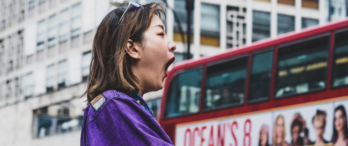 Une femme en train de bailler devant un bus