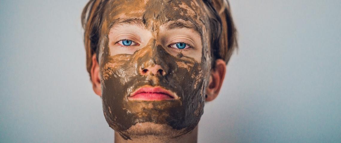 Un homme avec un masque à l'argile sur le visage