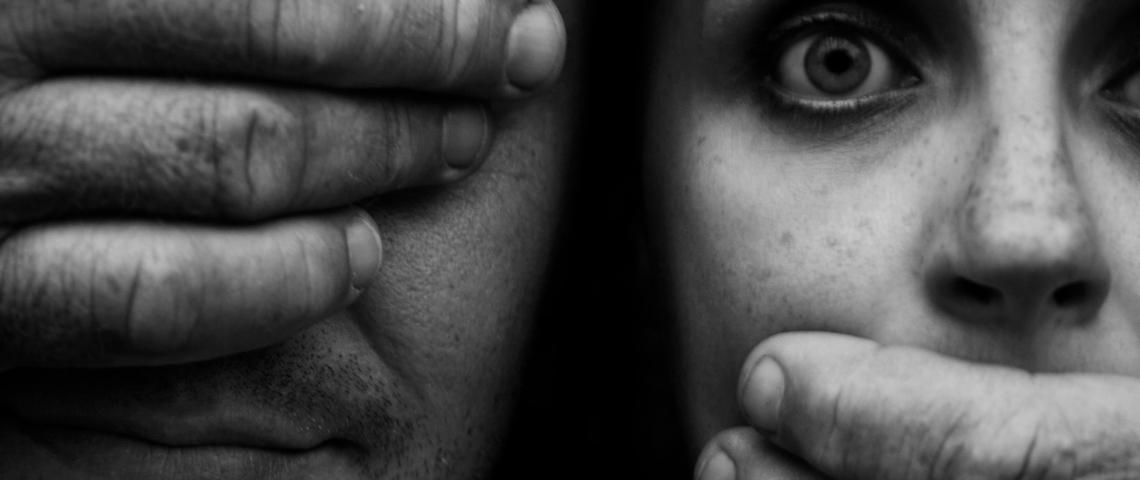 Un homme aux yeux bandés ferme la bouche d'une jeune femme