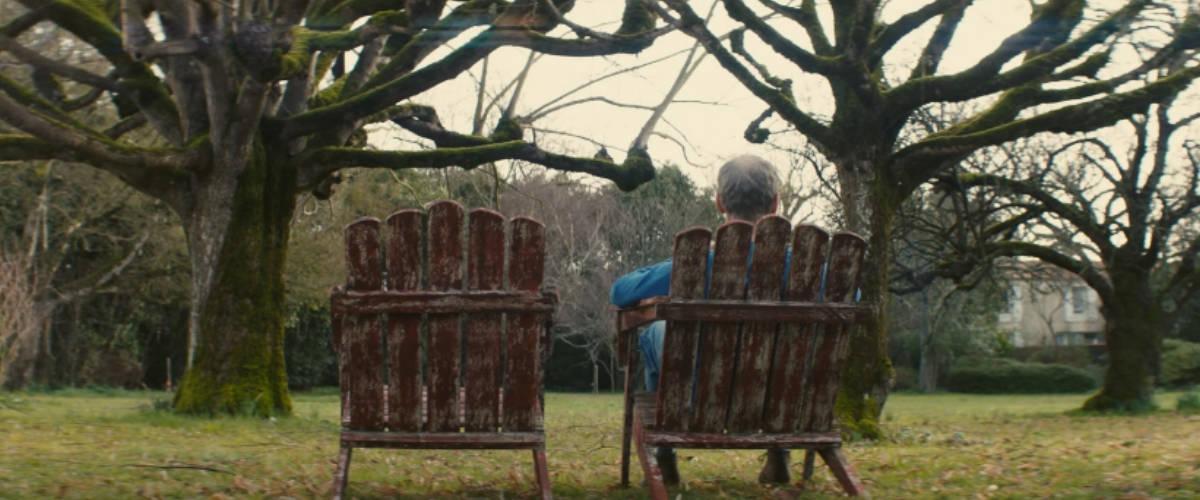 Un homme assis dans un jardin avec une chaise vide à côté d'eux