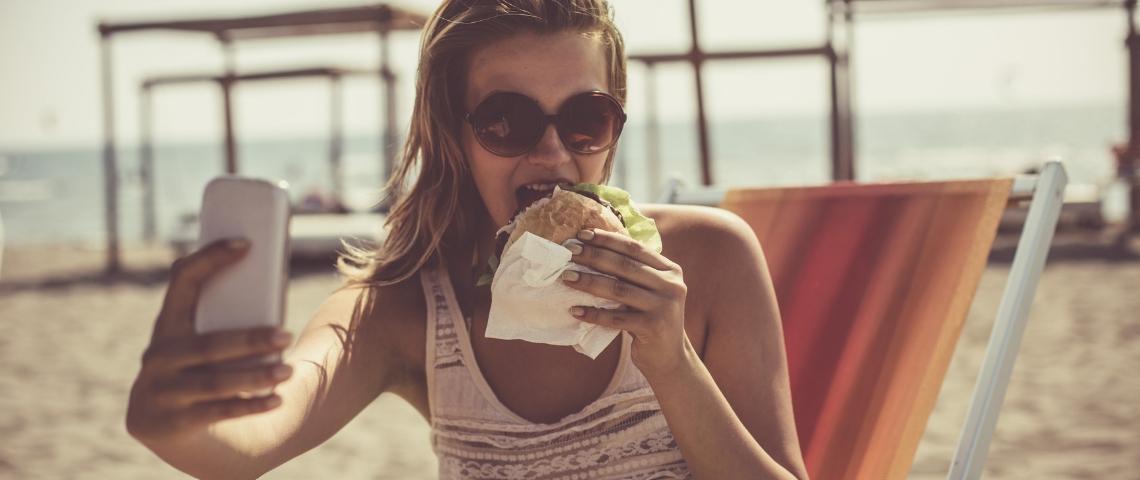 Une femme à la plage qui prend un selfie en mangeant un burger