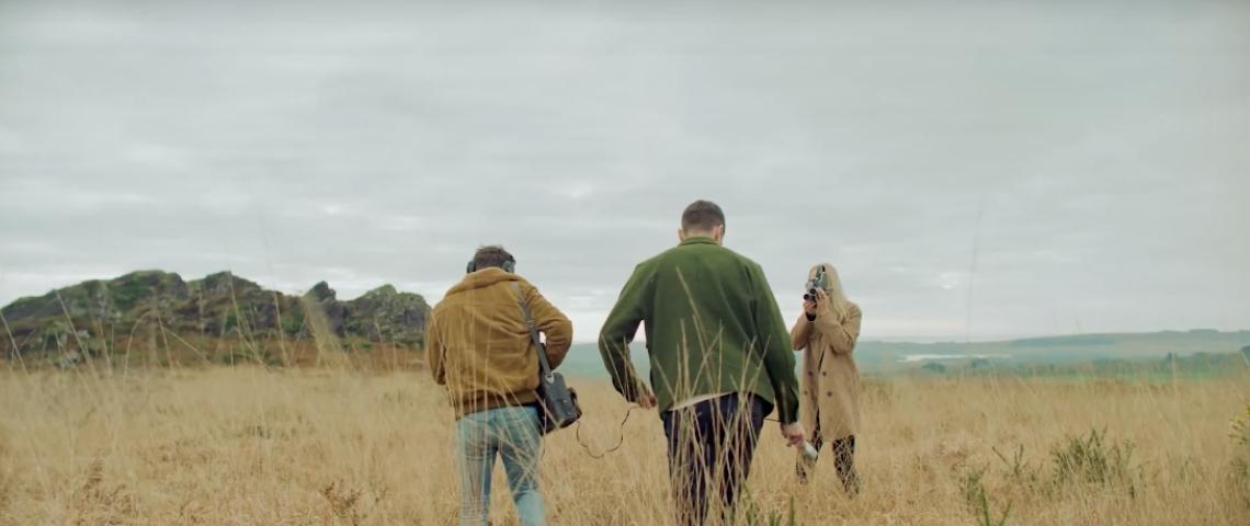 Deux hommes et une femme dans un champ