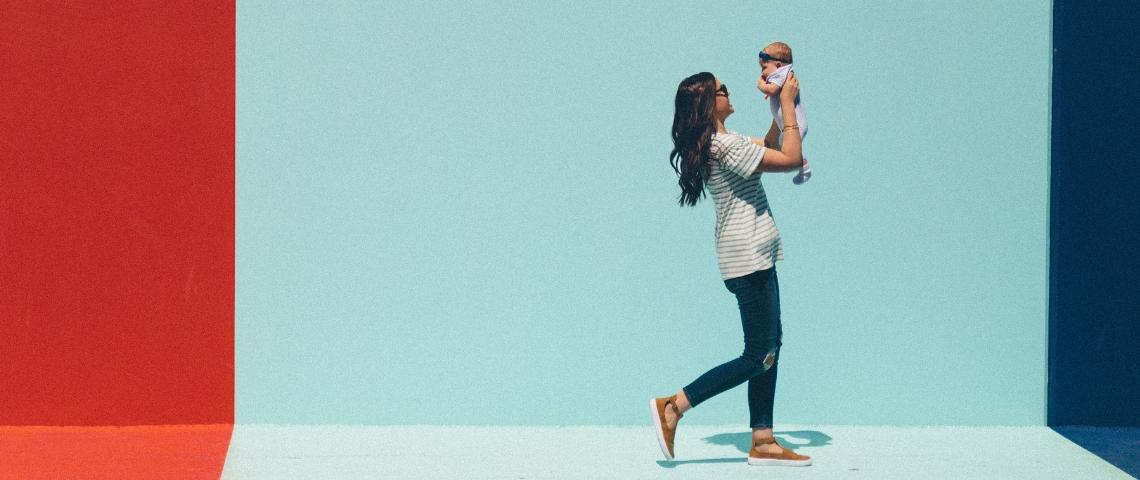 Une femme qui marche avec un enfant dans les bras