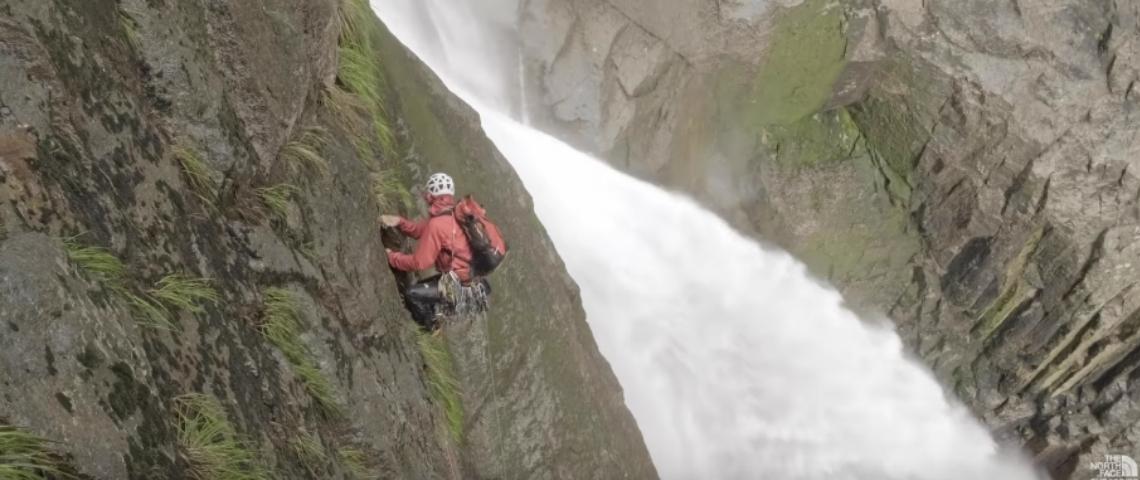 Un homme qui escalade une cascade