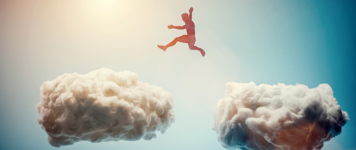 Un homme saute de nuages en nuages dans le ciel