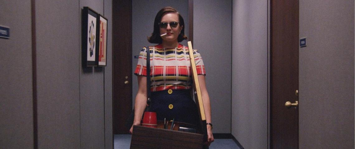 Une femme avec une cigarette part de son bureau carton à la main