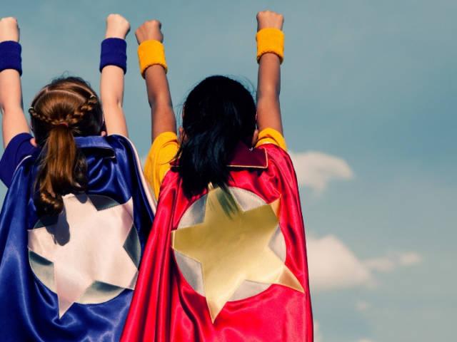 Deux petites filles habillées en super-héroïnes de dos