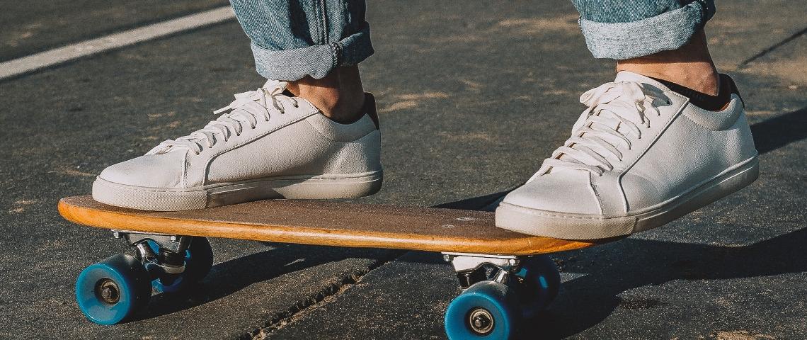 Des baskets blanches sur un skateboard