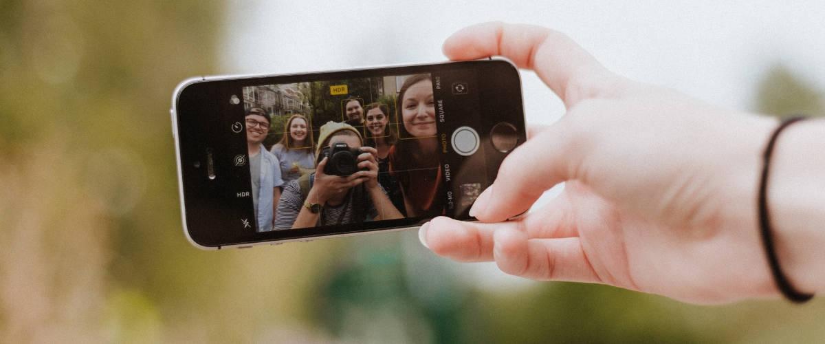 Une main qui tient un smartphone en train de prendre un photo un groupe de personnes