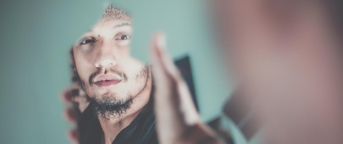Un homme se regarde dans un miroir cassé