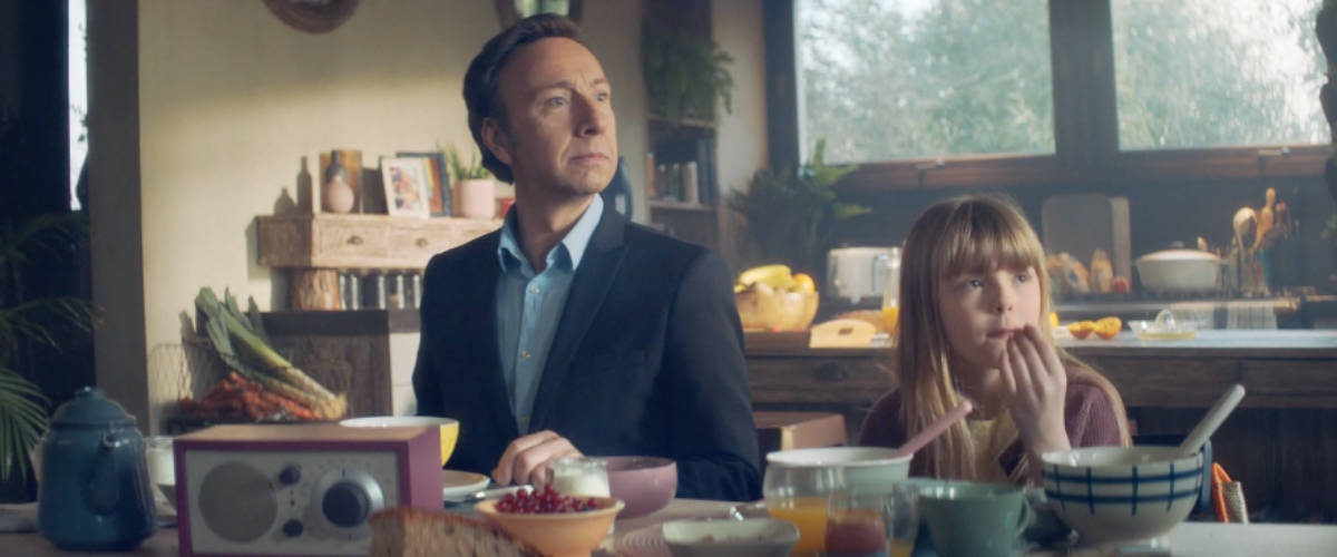 Stéphane Bern et une petite fille en train de prendre le petit-déjeuner