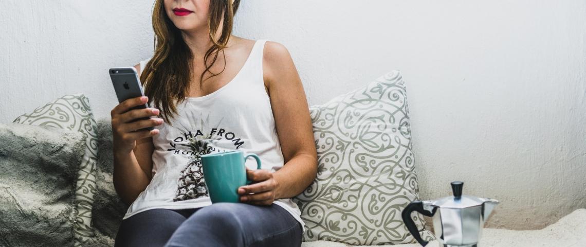 Une femme sur un canapé avec un smartphone à la main