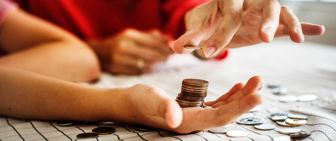 Une main qui donne des pièces à une autre