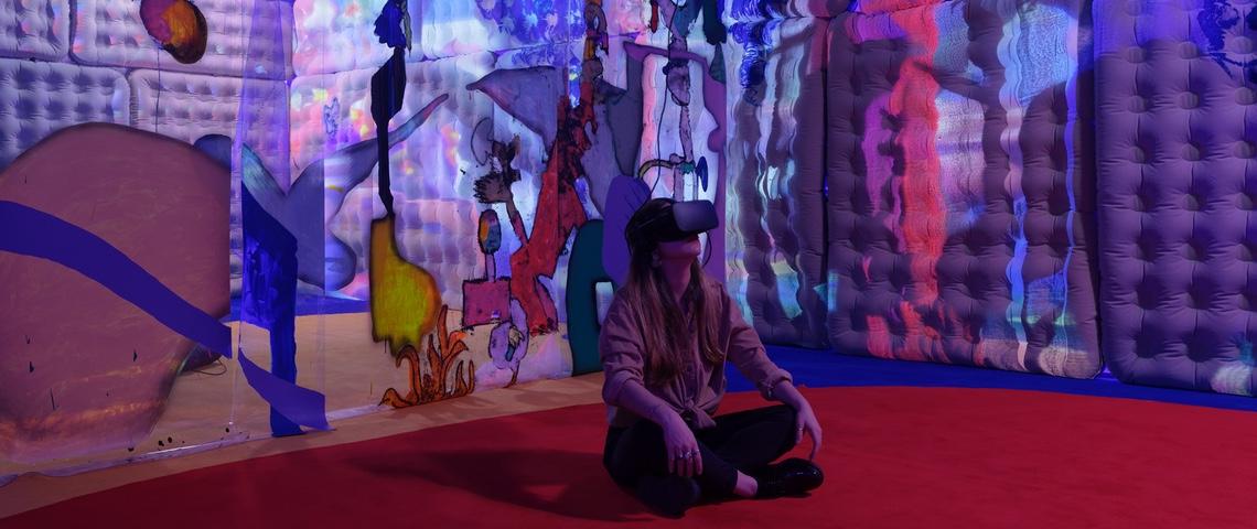 Jeune femme assise par terre dans un musée avec un casque de réalité virtuelle.