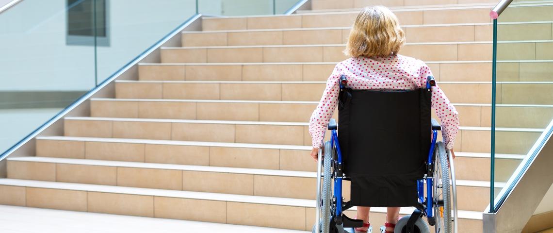 Femme en fauteuil roulant devant des escaliers
