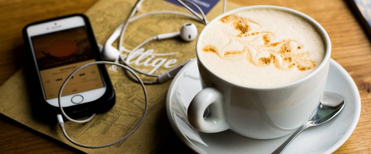Tasse de cappuccino et smartphone avec des écouteurs sur une table.