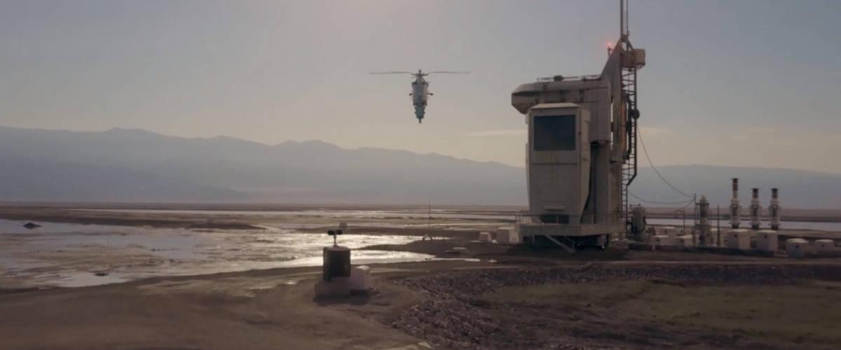 Plan large d'un desert en présence d'un engin volant et d'une usine
