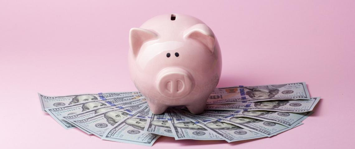 Une tirelire cochon derrière une liasse de billets, sur un fond rose