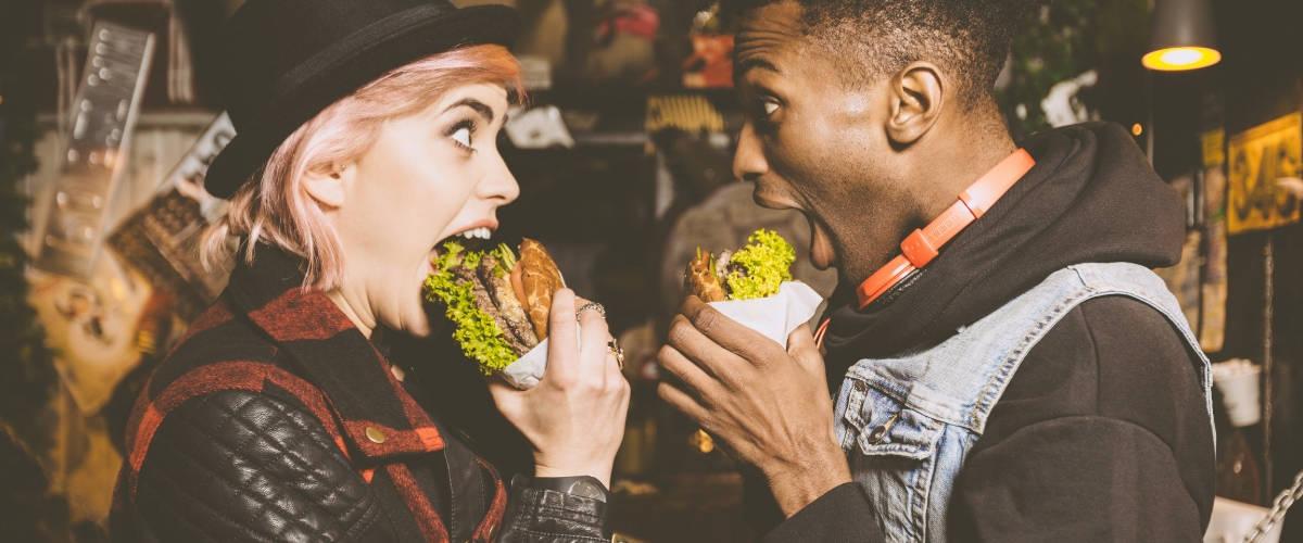 Une femme blanche et un homme noir qui mangent un burger en se regardant