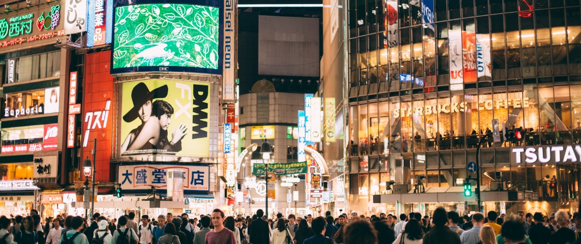 La foule dans une rue avec des écrans sur les immeubles