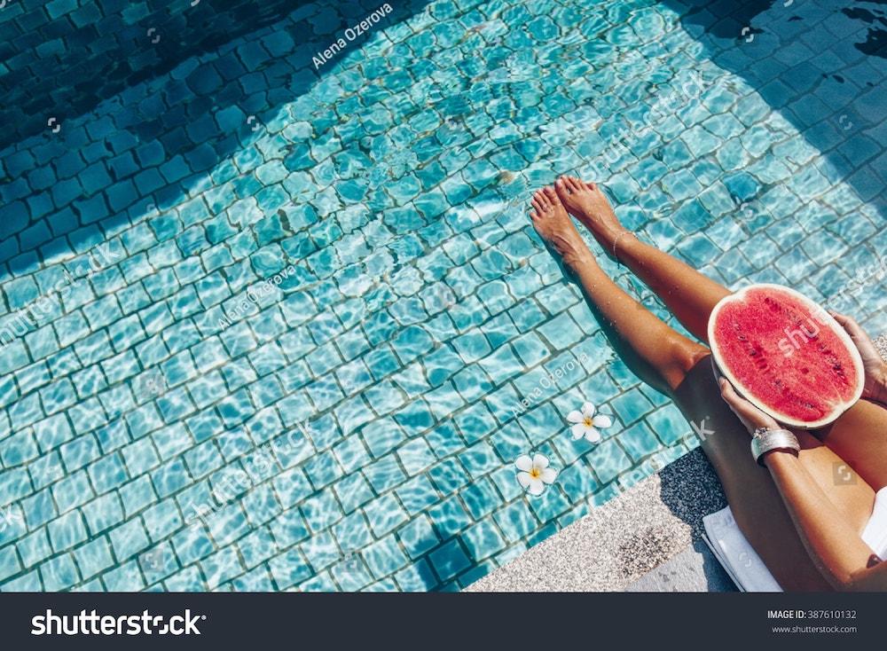 une fille tient une pastèque dans une piscine