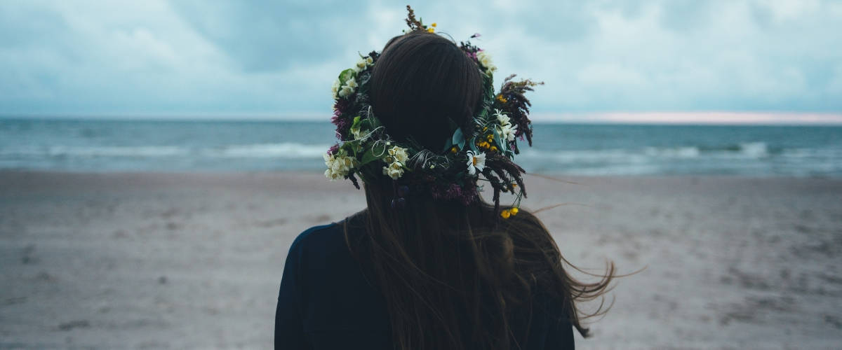 Une femme brune de dos face à la mer avec une couronne de fleurs dans les cheveux