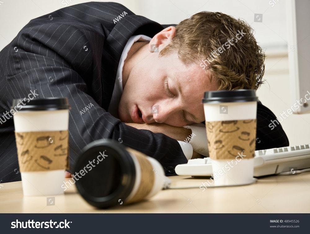 un homme dort sur son bureau