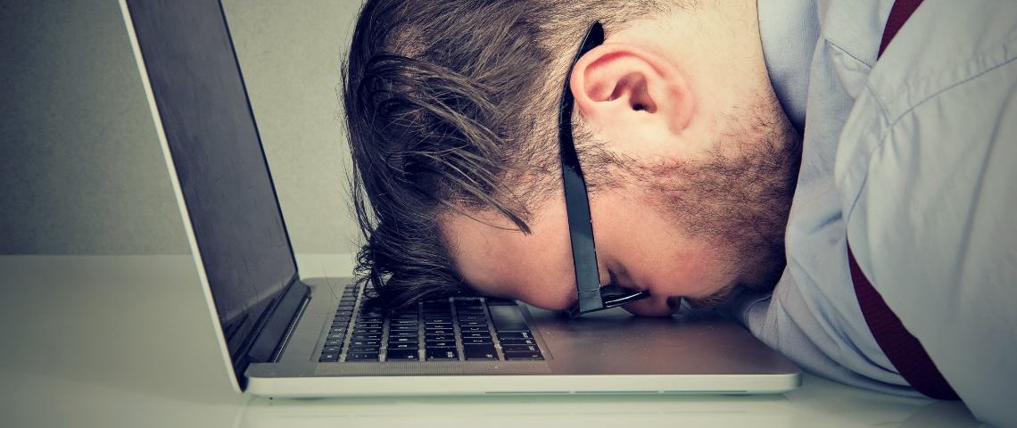 un homme dort sur son clavier au bureau