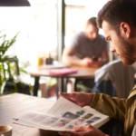 un homme lit un magazine dans un bar
