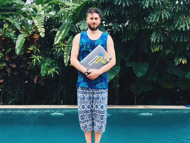 Un homme en train de tenir un ordinateur devant une piscine