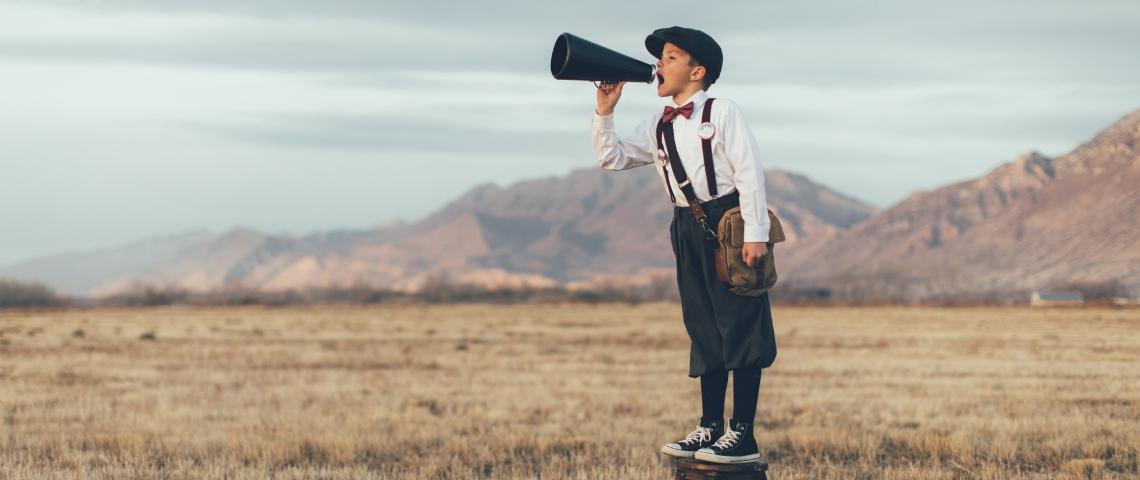 un petit garçon dans un champ sur un tabouret qui parle dans un haut parleur