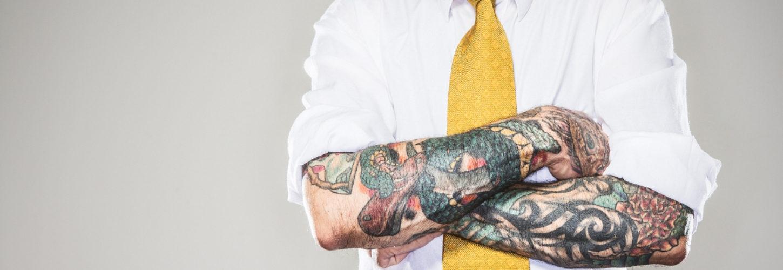 Un homme avec un cravate jaune et des tatouages sur les bras