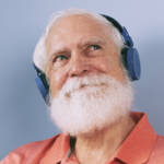 Un vieil homme à barbe blanche écoute de la musique à travers un casque audio